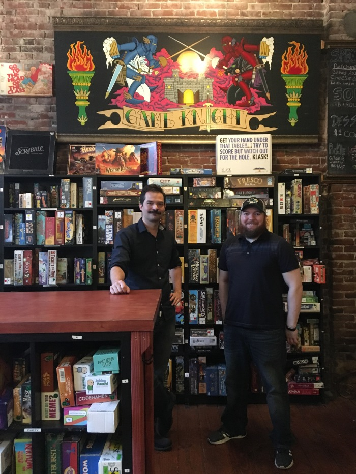 Two people in black shirts and pants stand in front of a wall of shelves containing board games.